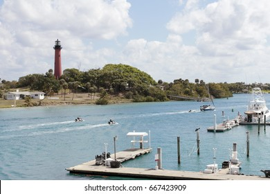 Jupiter, FL, USA - March 30, 2017: Boat docks and people on jet skis, boats and paddle boards in the Loxahatchee River. People on watercraft on Jupiter Inlet near a lighthouse.