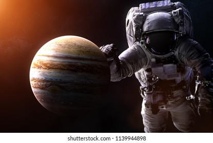 Jupiter on a blurred background with a giant astronaut. Image in 5K resolution for desktop wallpaper. Elements of the image are furnished by NASA