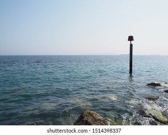 Jurassic Coast, Dorset/ UK - June 29 2019: marker pole in the sea at the end of a breakwater sticking out into the sea on a beach on the Jurassic Coast (dinosaur fossils); sunny day; blue sky