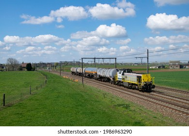 JURBISE, Belgium - April 13, 2021: LINEAS Belgian Yellow-Grey Diesel (Shunting) Locomotive with Tank Wagon Freight Train in Green, Rural Area in Sunny Weather