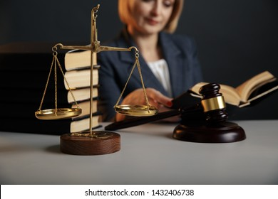 Juridical concept. Closeup picture of reading woman. Gavel and scale on the table.
