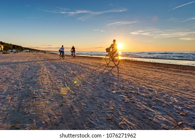 Jurmala beach with lonely girl figure on bicycle. Vacation concept