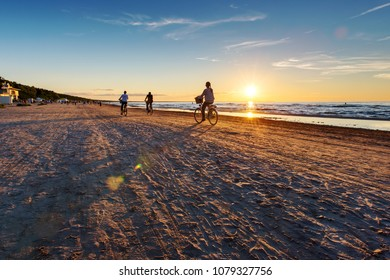 Jurmala beach with lonely girl figure on bicycle. Sunset time.Vacation concept