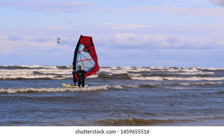 Jurmala, Latvia - 06/06/2019 EDITORIAL: Professional surfer in the wind preparing the wind in the sea to the ocean. Windsurfer catches the wave in a storm. Concept of: Sport, Lifestyle, Board, Waves.