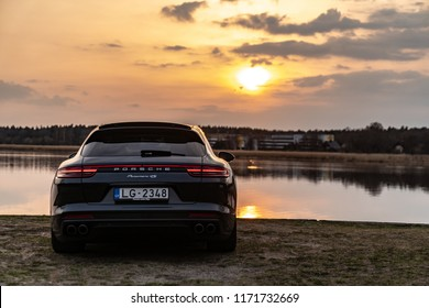 Jurmala, Latvia 1 September 2018 Porsche Panamera Sport Turismo Second generation (971), stands by river landscape at sunset background