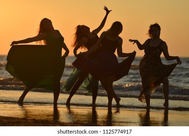 Jurmala, Latvia - August 23 2015: Silhouettes of four girls in dresses dancing on the beach of Baltic sea. Summer evening. Orange sunset.