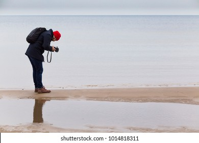 JURMALA, LATVIA - JANUARY 5, 2018: Taking an image photographer on Jurmala's winter beach.