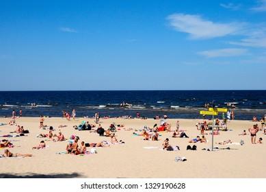 Jurmala, Latvia - July 25, 2018 - People chilling on the beach on Riga bay of the Baltic Sea in Jurmala resort town of Latvia
