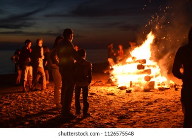 Jurmala, Latvia - June 24 2016: Father and son and group of people celebrating Ligo (midsummer holiday) on the beach of Baltic sea at night by a large campfire.