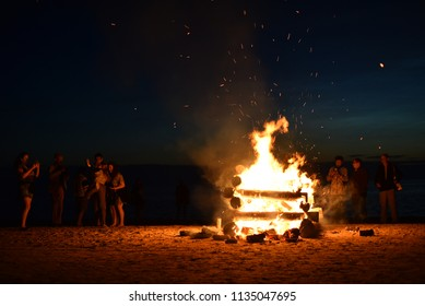 Jurmala, Latvia - June 24 2016: Group of people by a large campfire on the beach of Baltic sea at night. Midsummer holiday (Ligo).