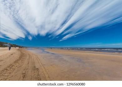 Jurmala, Latvia - May 7, 2017: People are walking  on sandy beach on the Baltic Sea in Jurmala in Latvia.
