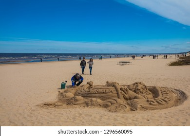 Jurmala, Latvia - May 7, 2017: Man is sculpturing the figure from sand  and people are walking  on sandy beach on the Baltic Sea in Jurmala in Latvia.