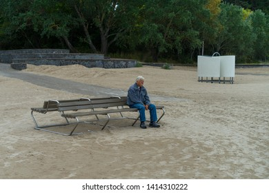 Jurmala / Latvia - September 08 2017: Elderly man sitting on the bench. Famous sandy Jurmala beach in fall. A favorite holiday-resort and tourist destination for high-level Communist Party officials.
