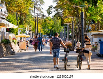 Jurmala, Latvia - September 2, 2018: Young couple on bicycles in Jurmala in Latvia.