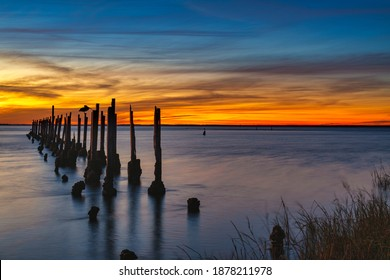 Just after sunset at St. Marks Wildlife Refuge. Forground is a brown pelican standing on a post from a dilapidated pier.
