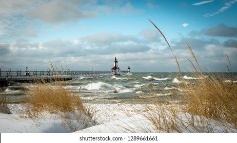 Just after a winter snow storm blanketed the land the waters of lake Michigan were rough because of the wind and standing steady and true is the north pier lighthouse of St. Joseph Michigan