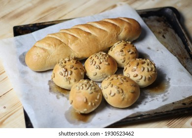 Just baked bread loaf and buns with sunflower seeds on baking paper and oven tray