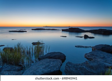 Just before the sunrise over the old lighthouse in the horizon. Gotland in the Baltic Sea.