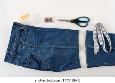 Just cutted blue denip shorts, measuring tape, scissors and sewing pin on a white table. Shorten the jeans with scissors and sewing pin. DIY summer clothes. Top view.