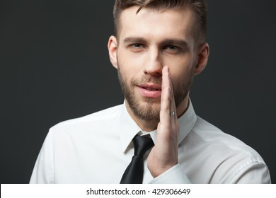 Just don`t tell anyone! Young businessman whispering trade secrets isolated on dark gray background.