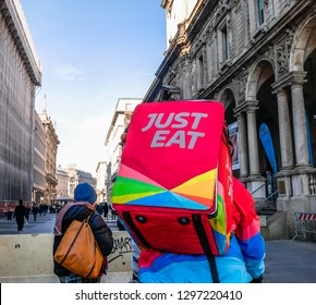 Just Eat Delivery Man Colored on his Bicycle in the city Center of Milan near Piazza Duomo. Italian Food Delivery. Milan, Italy-January 2019