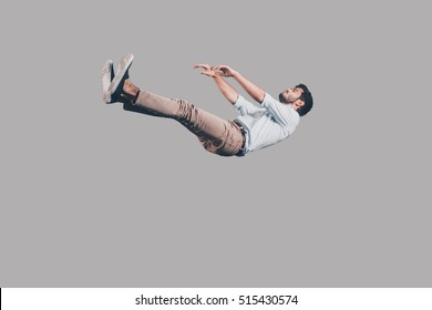 Just falling down. Mid-air shot of handsome young man falling against grey background