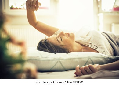 Just five more minutes. Young woman waking up in bed. Space for copy.