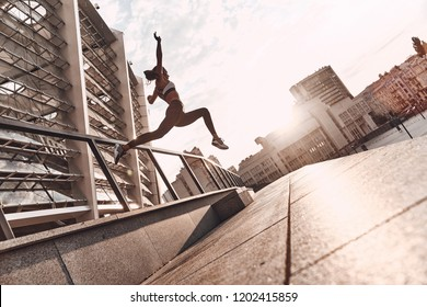 Just flying. Full length of modern young woman in sports clothing jumping while exercising outdoors