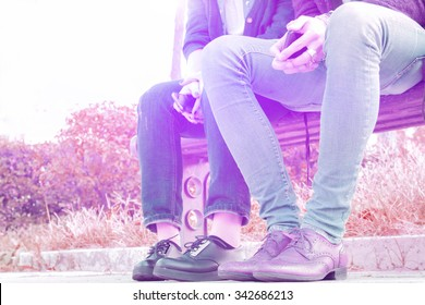 just friends. a shy couple at first meeting, sitting on a park bench. concept of friendship and affection. partial view from the bottom vintage look with attractive pink to purple color tones