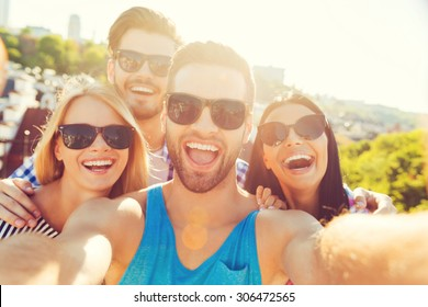 Just for fun. Group of cheerful young people bonding to each other and making selfieon camera while having fun on the roof