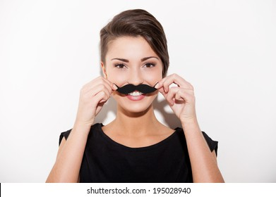 Just having fun. Beautiful young short hair woman holding fake mustache on her face and smiling