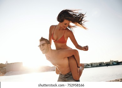 Just having fun.  Handsome young man giving his attractive girlfriend a piggy back ride while walking on the beach