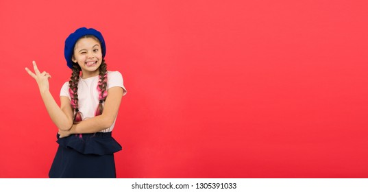Just having fun. Summer holidays. Kid little cute fashion girl posing with long braids and hat red background. Child small girl happy smiling baby. Happy childhood. Advertisement happy kid copy space.