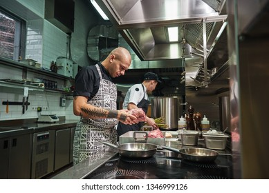 Just high quality. Concentrated chef with tattoos on his arms holding fresh red meat ant thinking about future dish