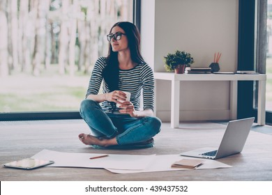 Just inspired. Confident young beautiful woman holding coffee cup and smiling while sitting on the floor at home with blueprint laying near her