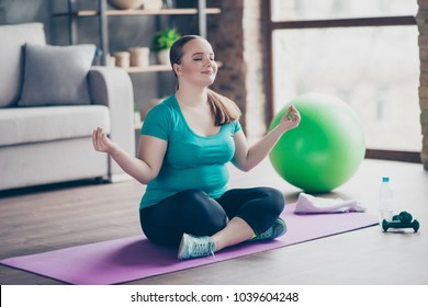 Just keep calm and do sport! Peace rest relaxation vitality concept. Cheerful curvy fatty concentrated oversize with flabby belly is sitting is lotus position on purple mat on the floor at home