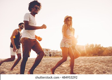 Just keep running! Group of young cheerful people running along the beach and looking happy