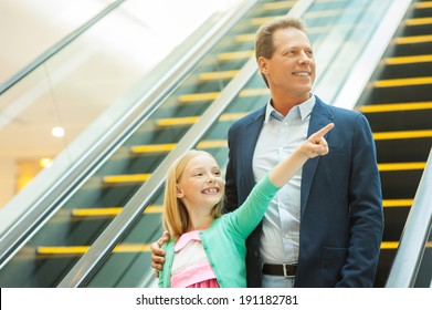 Just look over there! Cheerful father and daughter moving down by escalator while little girl pointing away and smiling