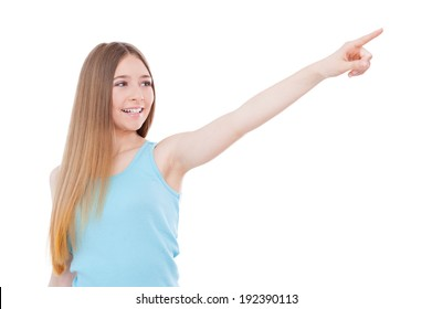 Just look over there! Happy teenage girl pointing away and smiling while standing isolated on white
