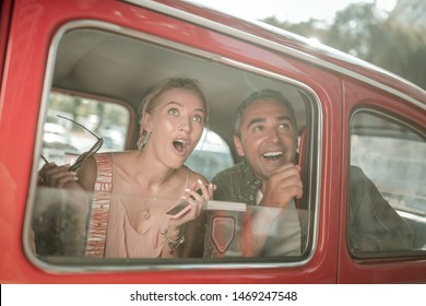 Just look at this. Amazed woman sitting with her husband in the car and looking out of the window with her mouth opened.