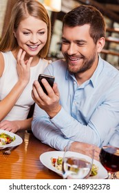 Just look at this! Beautiful young loving couple enjoying time in restaurant together while man showing something at his mobile phone and smiling