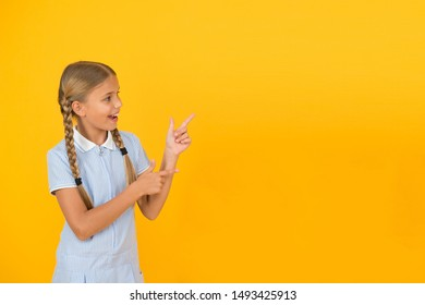 Just look at this. Happy little school girl pointing finger at yellow background copy space. Back to school. Attention concept. Advertisement model. Schoolgirl presenting school product. Positive kid.