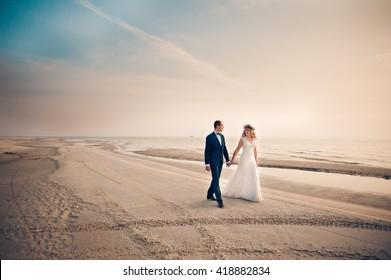 Just married bride and groom walking on the beach in their honeymoon