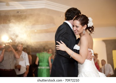 Just married couple dancing in front of their unrecognizable friends.
