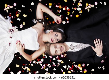 Just married couple lying on black backgruond with flower petals, a lot of copyspace available