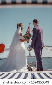 Just married couple on yacht. Happy bride and groom on their wedding day. Back view.