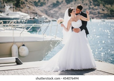Just married couple posing in small cove. Happy bride and groom on their wedding day
