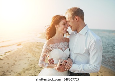 Just married couple running on a sandy beach