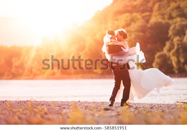 Just Married Couple Spinning on Beach Riverside Background