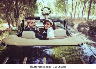 Just married couple together in an old car